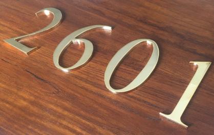 Números en latón baño de oro montados sobre madera de sapelli